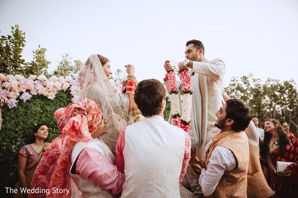 Indian couple exchanging garlands ritual.