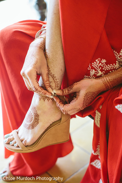 Indian bride putting her shoes on.