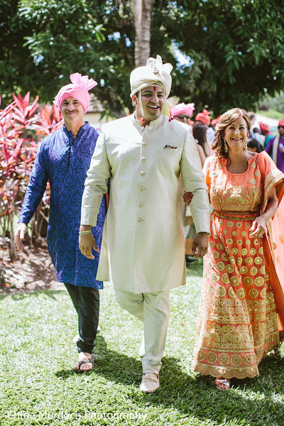 Indian groom walking with bride's parents.