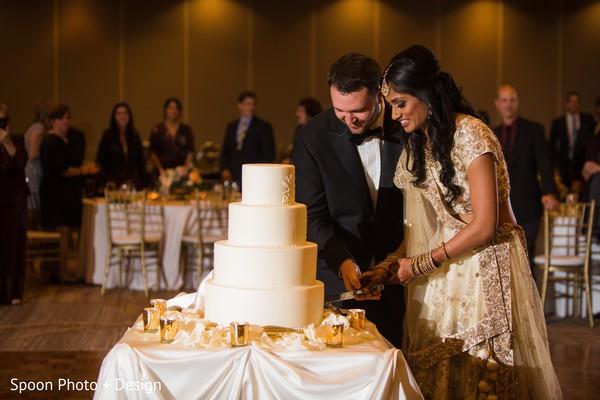 Indian wedding couple cutting the cake.