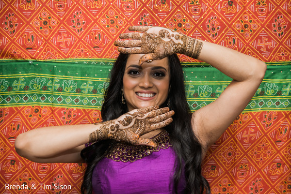 Dazzling indian bride showing her mehndi art.