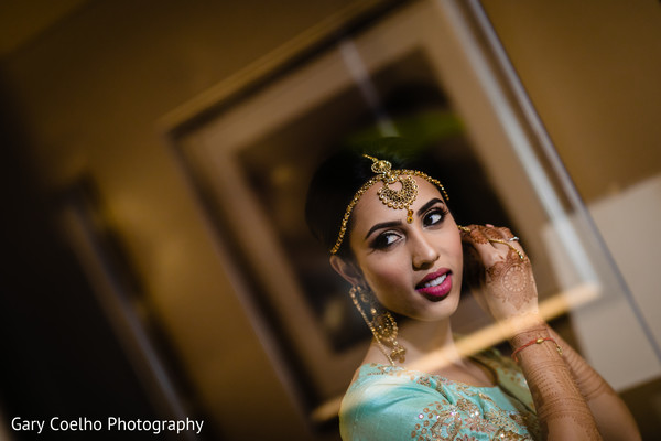 Indian bride putting her earings on.