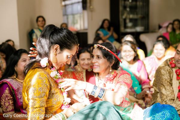 Indian bride getting a garland at her haldi rituals.