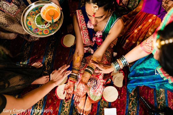 Indian bride getting turmeric paste on .