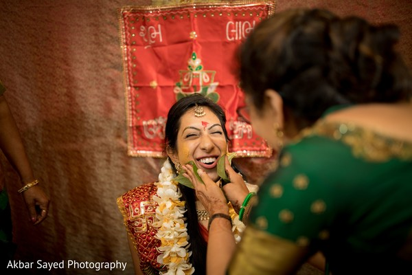 Indian bride getting the yellow turmeric paste on.