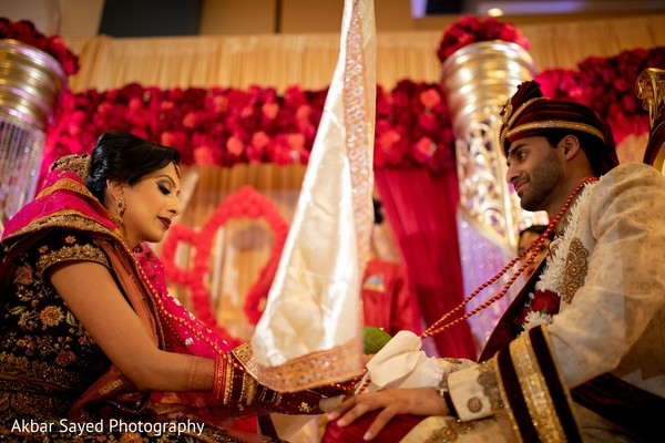 Indian groom covered by antarpat at ceremony.
