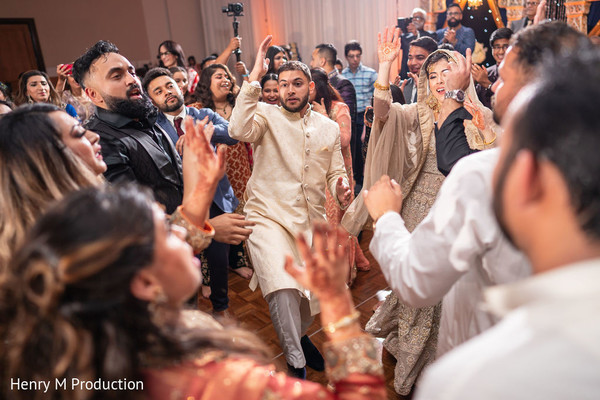Indian newlyweds dancing with guests