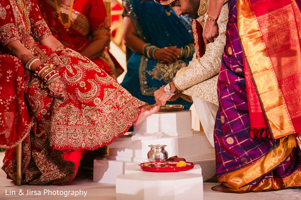 Indian groom putting ring on bride's toe.