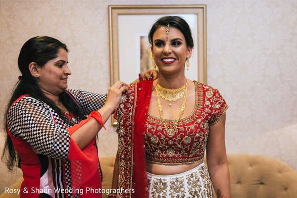Indian groom being helped by parents to get ready