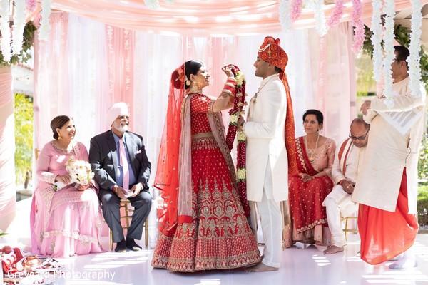 Indian bride  putting flower garland to groom