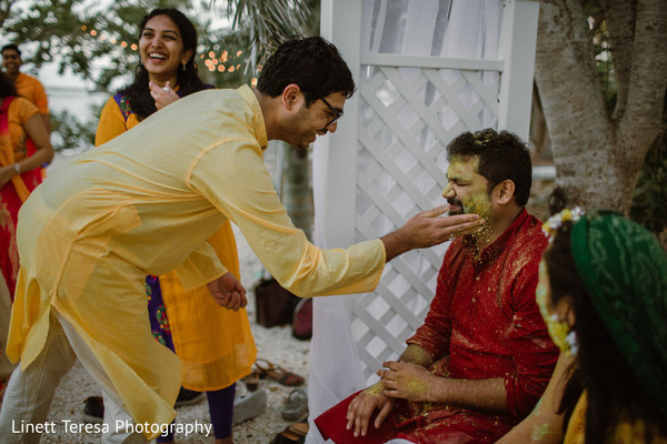 Indian groom getting turmeric paste on face.