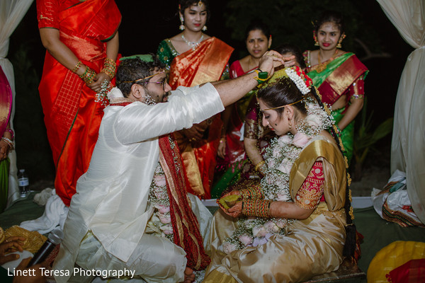 Indian groom pouring rice on to maharani's head.