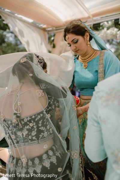 Indian bridesmaid helping bride.