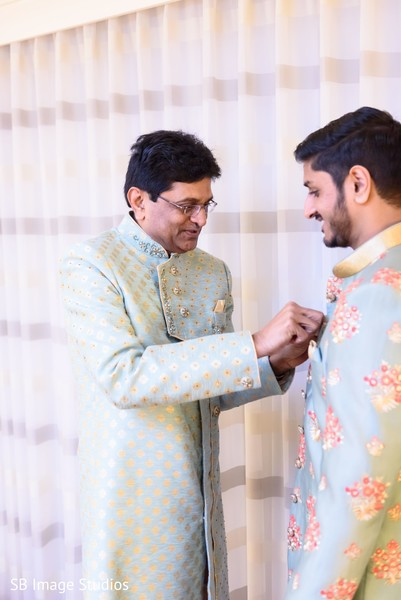 Indian groom's relative helping putting on his sherwani.