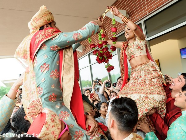 Enchanting Indian couple exchanging garlands at milni.