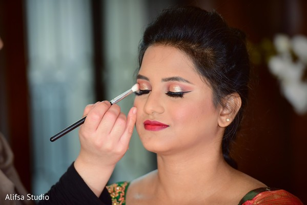Indian bride getting her wedding makeup done