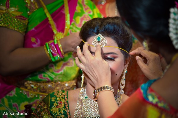 Indian bride getting the yellow thread.