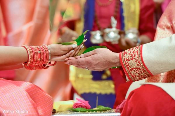 Closeup capture of Indian bride and groom's hands.