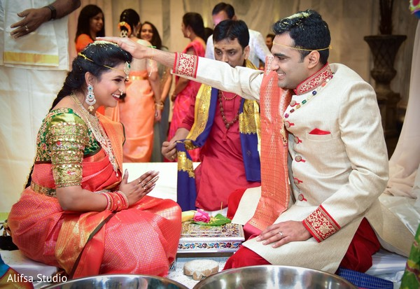 Indian groom putting rice to bride's head.