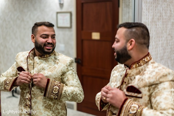 Charming Indian groom putting his ceremony outfit.