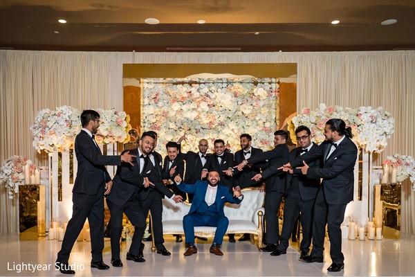 Joyful Indian groom with groomsmen at reception stage.