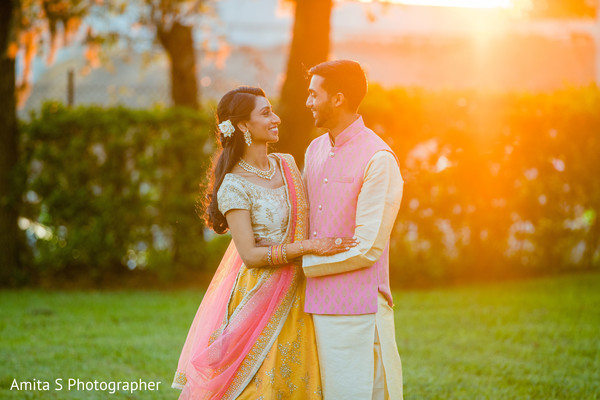 Outdoors Indian couple on their sangeet outfits.