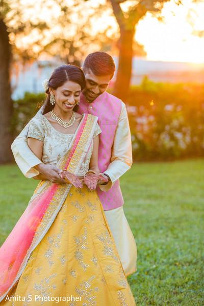 Lovely Indian bride and groom admiring mehndi art.
