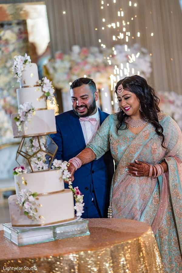 Sweet moment of Indian bride and groom cutting cake.