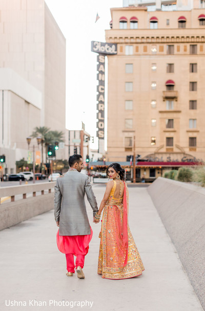 Indian bride and groom walking hand in hand.