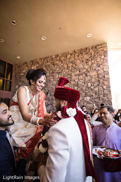 Indian bride putting a garland to groom at milni ritual.