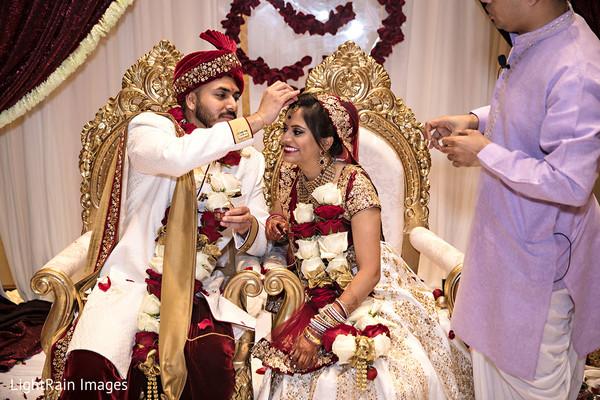 Indian groom putting the bindi on maharani's forehead.