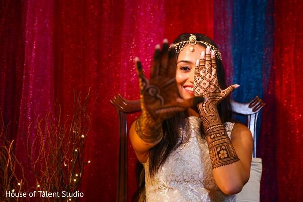 Elegant indian bride posing for photo at mehndi party.