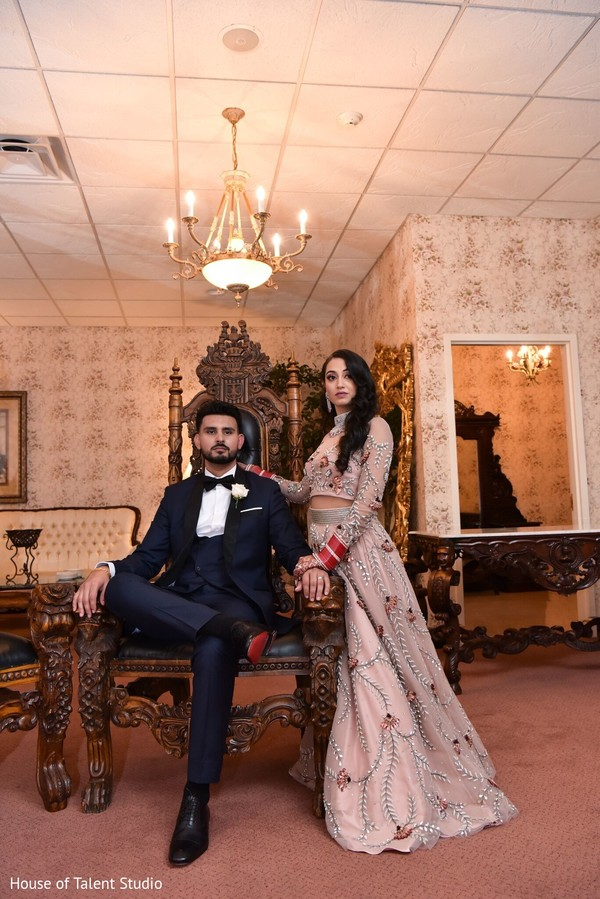 Elegant Indian couple posing with reception outfits.