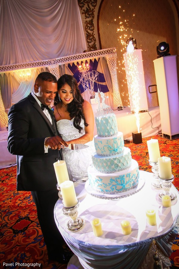 Lovely Indian lovebirds cutting cake together.
