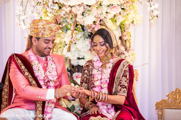 Indian groom putting wedding ring to bride capture.
