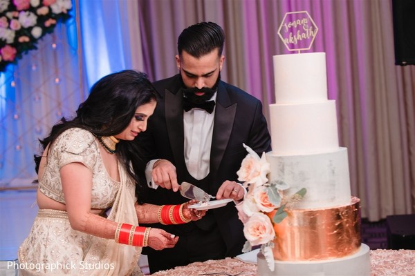 Lovely Indian bride and Indian groom cutting the cake.