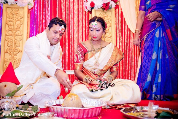 Rajah putting rice to wedding ceremony altar.