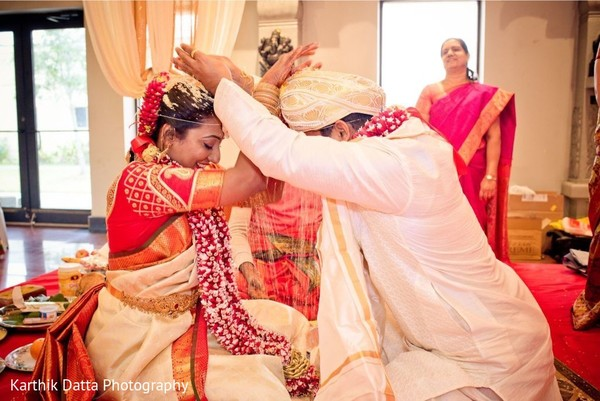 Traditional indian couple pouring rice on to each other.