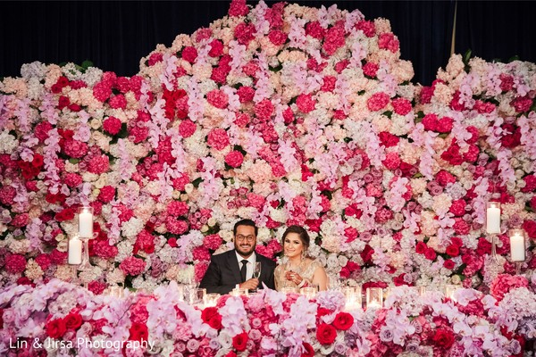 Indian couple seating at their stunning reception flowers table.