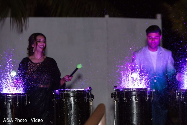 Indian bride and groom playing the drums
