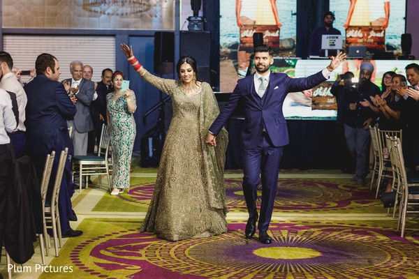 Elegant Indian bride and grooms entrance to wedding reception.