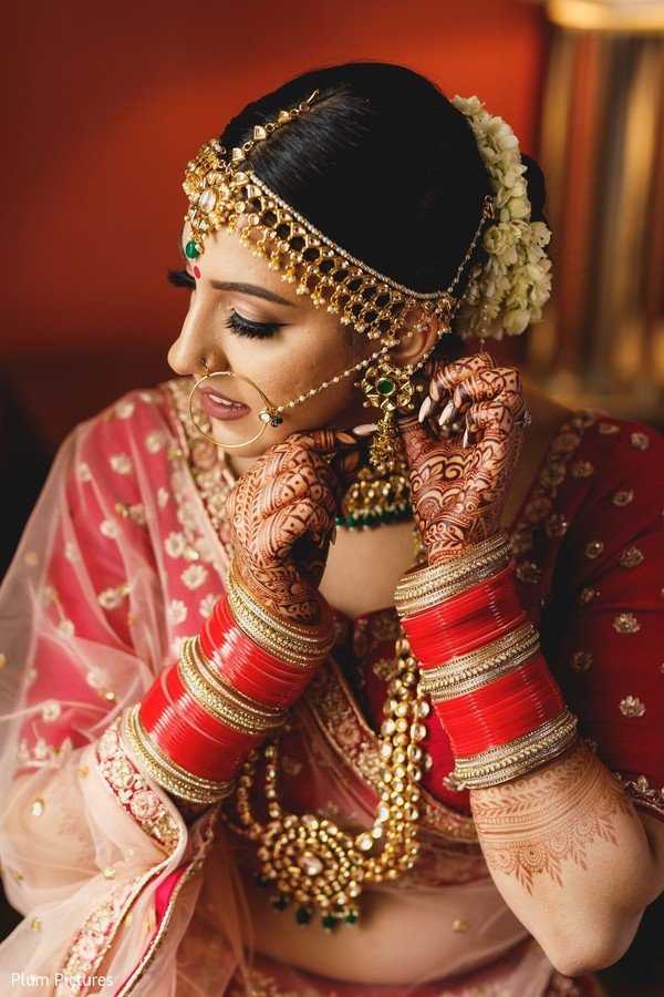 Enchanting Indian bride putting her jewelry on.
