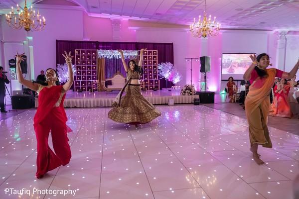 Indian bride dancing with bridesmaids at reception.