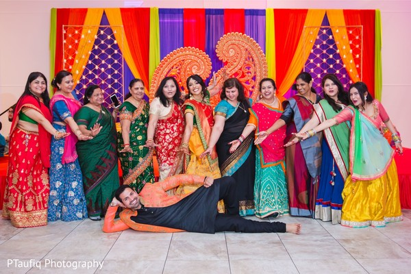 Fun capture of Indian groom with bride and bridesmaids.