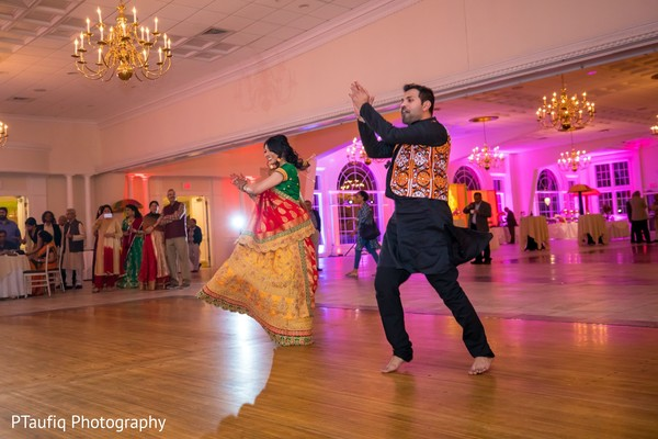 Enchanting Indian couple dancing at sangeet party.