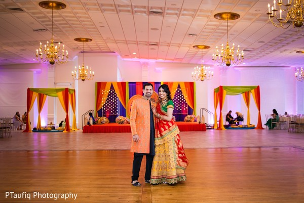 Lovely Indian couple posing at sangeet venue.
