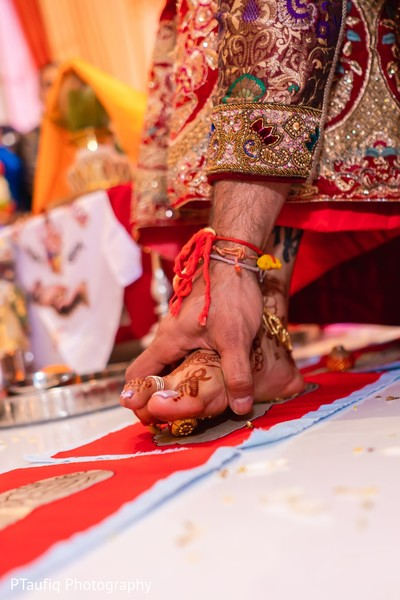 Indian couple when stepping on nuts with toes ritual.
