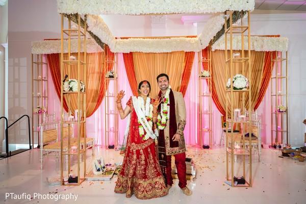 Indian lovebirds at their wedding ceremony mandap.
