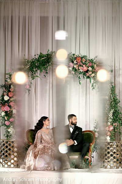 Groom and bride under the floral mandap.