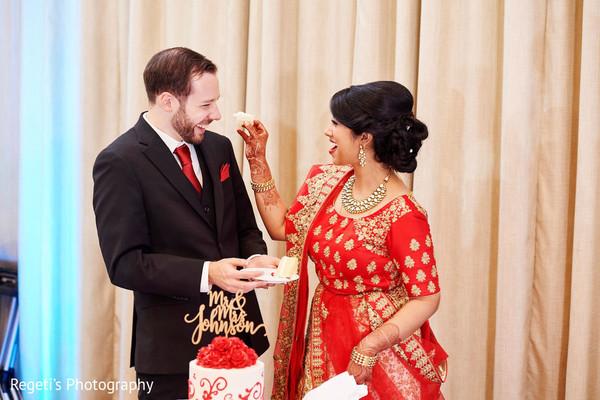 Indian bride giving the groom a taste of wedding cake.